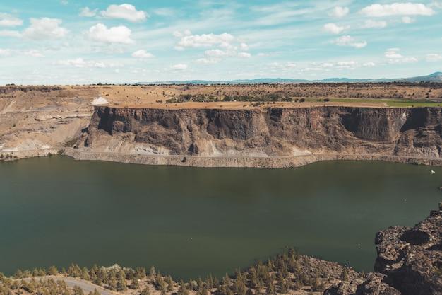 Пейзаж реки в окружении скал, покрытых зеленью под голубым небом и солнечным светом