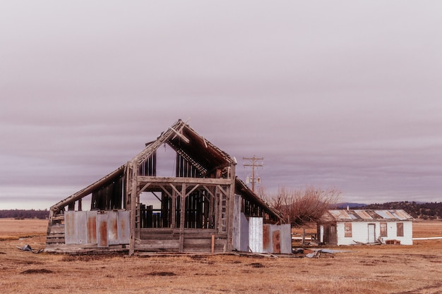 灰色の乾燥した砂漠のフィールドで半分造られた大きな木造建築物