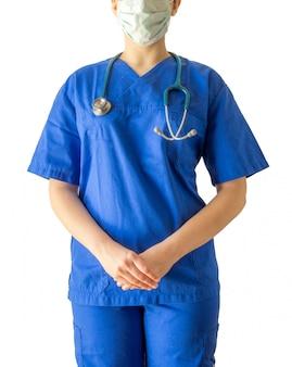 青い医療服と分離されたマスクの若い女性医師の肖像画