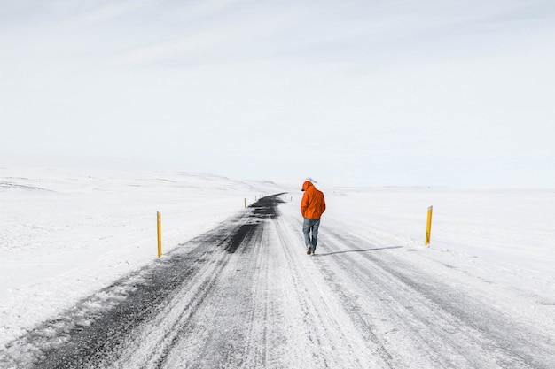 雪に覆われた高速道路の道路に沿って歩くオレンジ色のジャケットを着た男