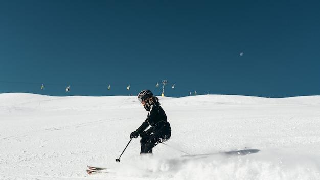 スキー服とヘルメットを身に着けている雪の表面でスキーをするスキーヤー
