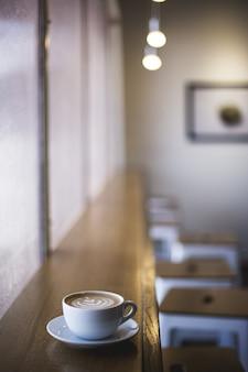 カフェの窓の棚にラテアートコーヒーの白いカップの垂直のクローズアップショット