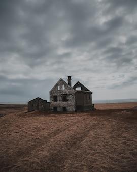 灰色の空の下で大きなブラウンフィールドにある古い廃屋と半分破壊された家の美しいショット