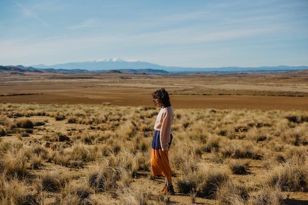 長袖のセーターと乾いた草で大きな茶色の野原に立っているロングスカートの女性