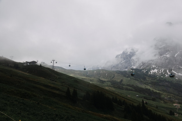 Дальний выстрел канатной дороги возле горы, в окружении деревьев
