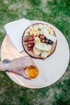 Вертикальный выборочный снимок человека, держащего стакан рядом с хлебом и фруктами на белой тарелке