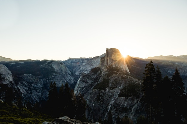 Воздушный выстрел из серых и черных скалистых гор с солнечными лучами в дневное время