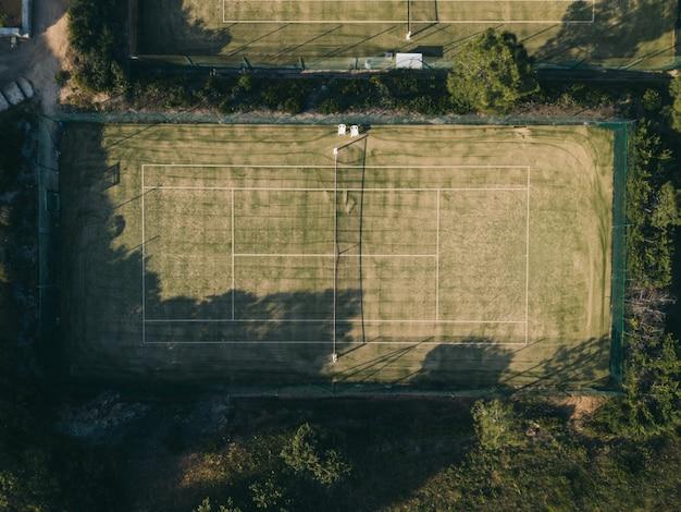 木々に囲まれたテニスコートの空中ショット