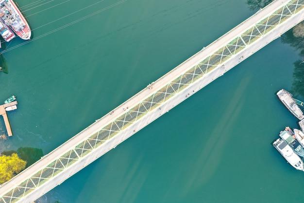 Длинный узкий мост, идущий через большую реку с кораблями, пришвартованными на побережье