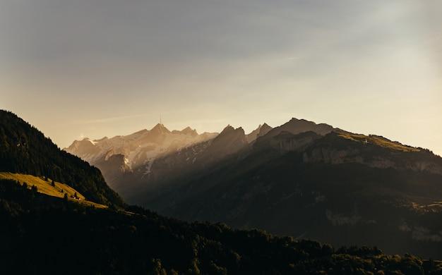 Широкий снимок гор и зеленых холмов под солнечным небом