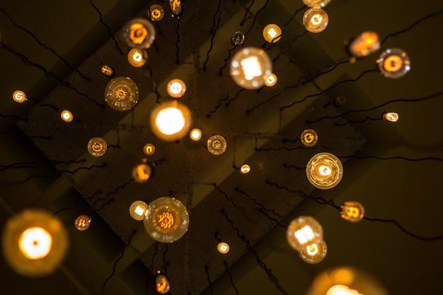 薄暗い光が天井からワイヤーにぶら下がっている多くのライトのアップショット