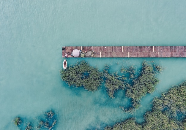 それの隣に漁船が付いている海岸で木製のドックのオーバーヘッドショット