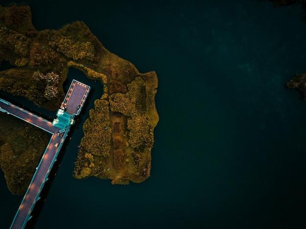 木の島に囲まれた海の上のドックの空中ショット