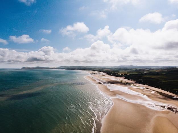 Воздушная съемка берега красивого пляжа около травянистого поля с облачным небом