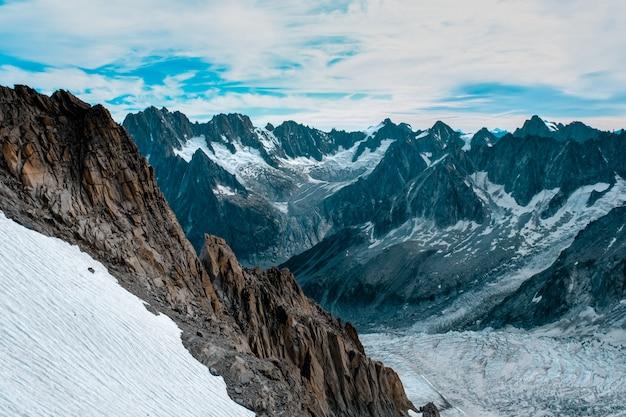 曇り空の下で雪に覆われた山々と雪に覆われた丘