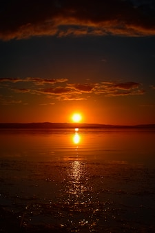 水の反射と空に雲と赤い夕焼けの美しい垂直ショット