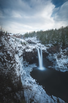 Красивая вертикальная съемка водопадов на ледниковой горе возле деревьев зимой