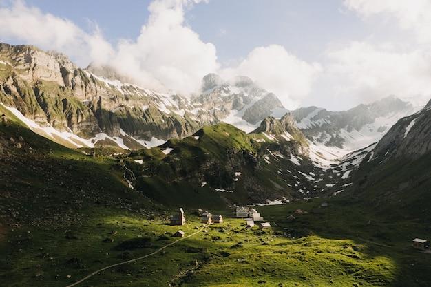 Красивый снимок зеленых гор, покрытых снегом под небом с белыми облаками
