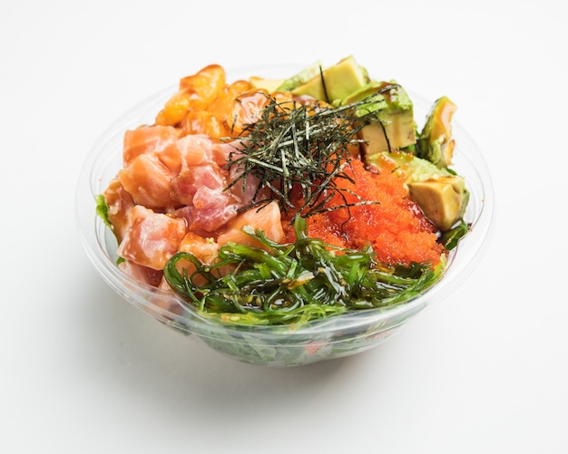 Крупным планом овощной салат с авокадо в стеклянную емкость на белой поверхности