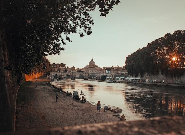 日没時にイタリア、ローマの水の体の横にある黒いコンクリート経路の美しいショット