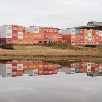 Красивый снимок воды, отражающей здания на берегу с ясным небом