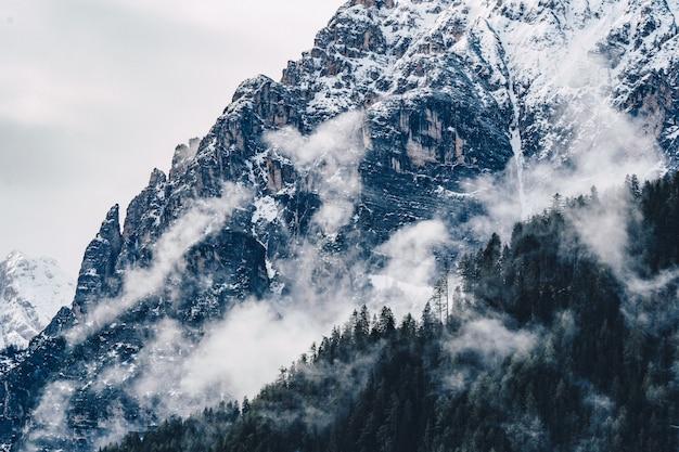 Красивый снимок туманных и облачно высоких скалистых гор
