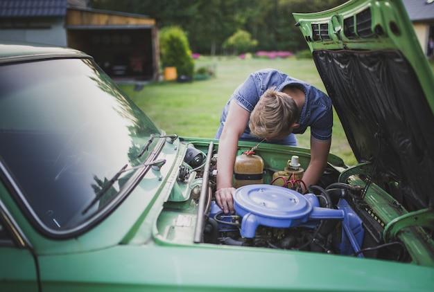 若いブロンドの男性は古い車を修理しようとして疲れて失望しました