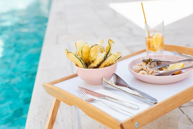 Селективный снимок крупным планом деревянного подноса, наполненного едой, серебром и стаканом