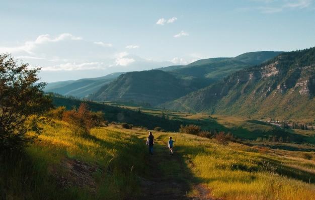 Красивая съемка малыша и мужчины гуляя на тропе посреди травянистых полей