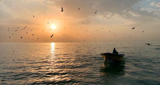 太陽が輝いている美しい海の真ん中にある小さな手漕ぎボートの男性