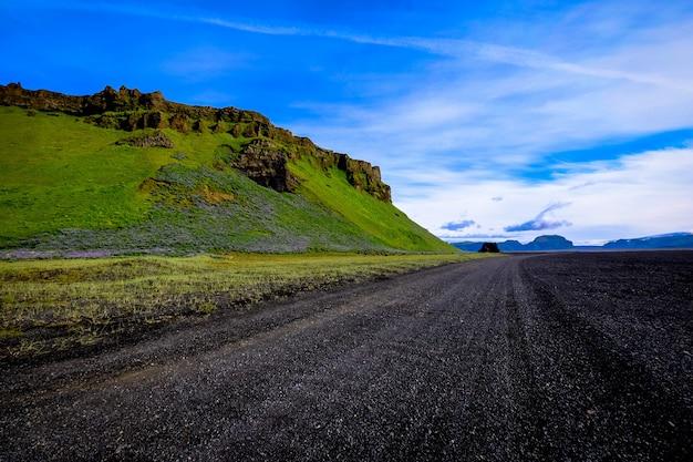 青空の下で草が茂った山の近くの道路