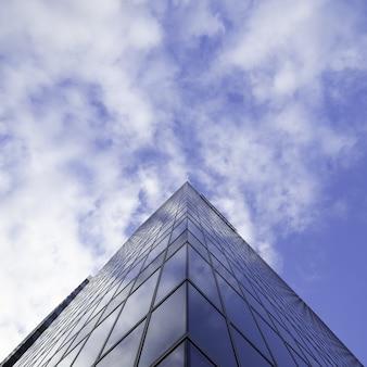 曇り空と背の高いガラスの超高層ビルの建物のローアングルショット