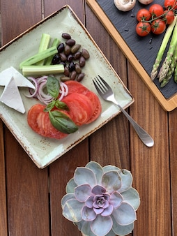フォークと正方形のプレートに豆とチーズのサラダのオーバーヘッドのクローズアップショット