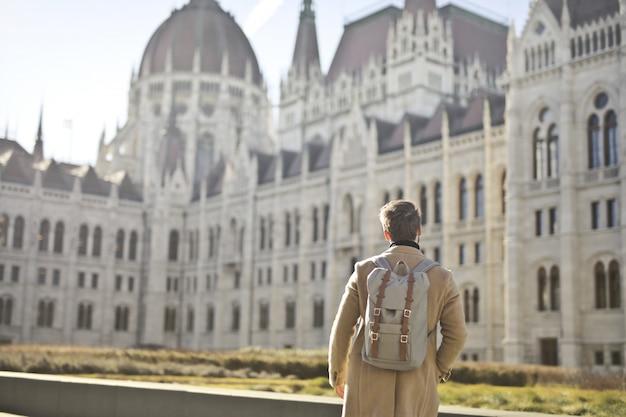 ハンガリーのブダペストの国会議事堂近くの茶色のコートとバックパックを着ている男性