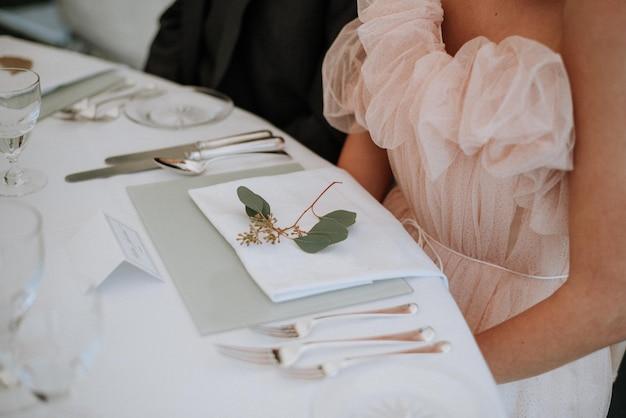 ナプキンと緑の葉が付いた結婚式のテーブルの前に座っているドレスを着ている女性