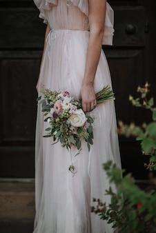 Вертикальный выброс невесты носить свадебное платье с букетом цветов