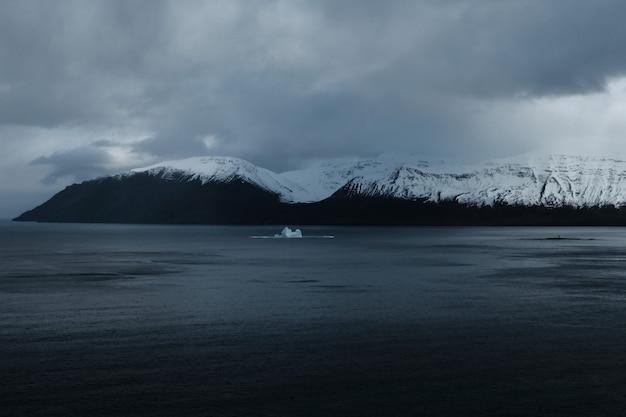 湖と暗い曇り空の美しい雪山