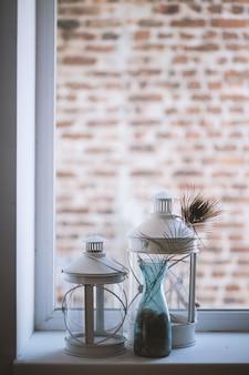 窓辺に大中型のガラスランタンランプの垂直選択的なクローズアップショット