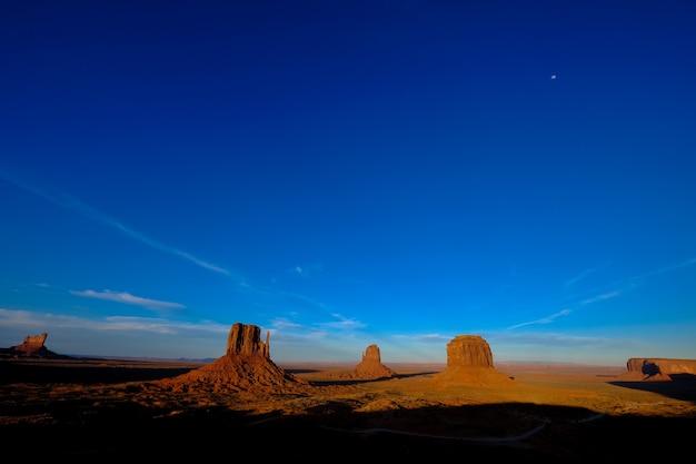 遠くに大きな崖がある砂漠の真ん中にある道の美しいショット