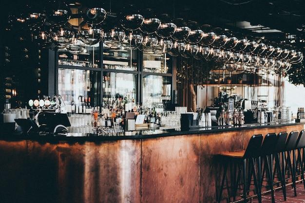 デンマーク、コペンハーゲンのスカンディックホテルのバーにあるディスプレイキャビネットのボトルとグラスのワイドショット