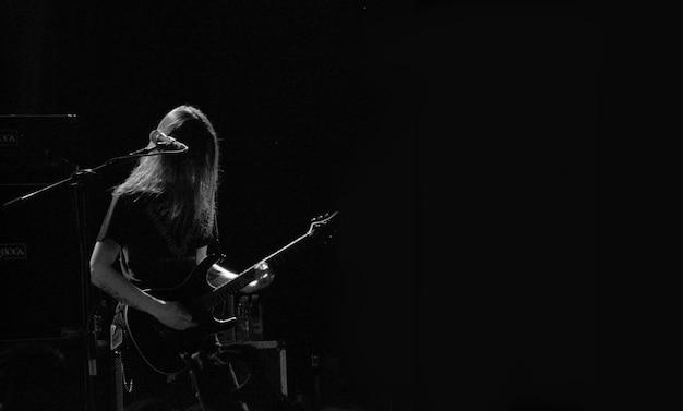 Мужской музыкант играет на гитаре на сцене возле микрофона в черно-белом