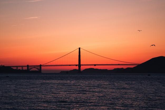 カリフォルニア州サンフランシスコの日没時に水域にゴールデンゲートブリッジのショット