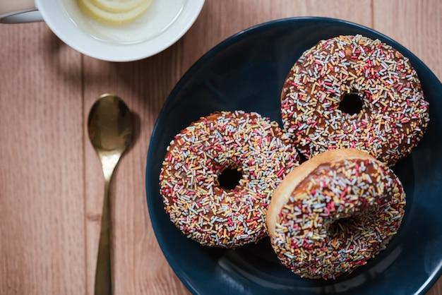 Крупным планом выстрел из вкусных посыпать пончики на деревянной поверхности и ложкой на стороне