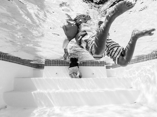 プールで泳いでいる人の黒と白の写真