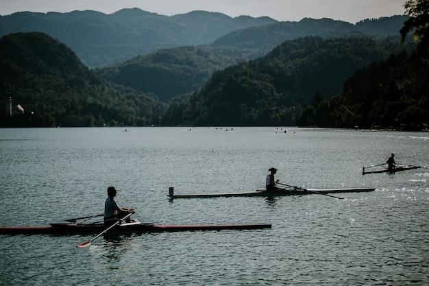 Красивая съемка людей ехать шлюпки на воде с заросшими лесом горами