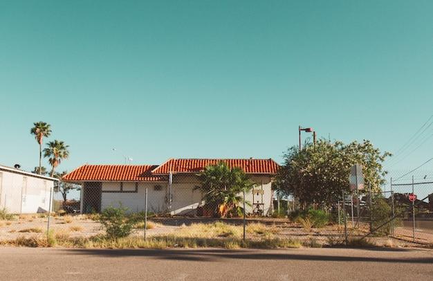 澄んだ空とその周りのフェンスのある家