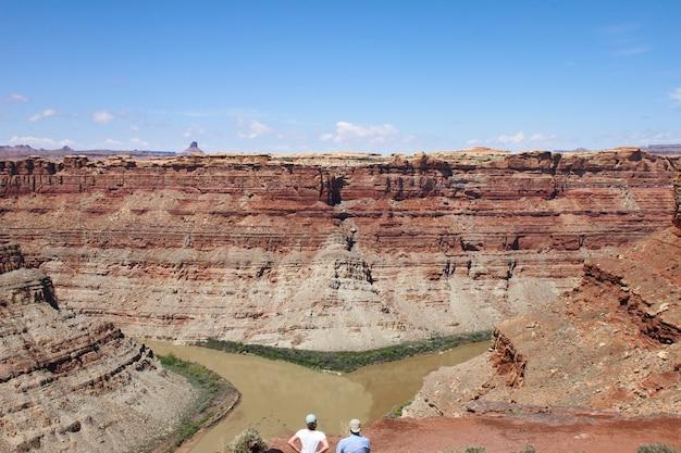 昼間に砂漠の崖に向かっている丘の上に立っている人の空中ショット