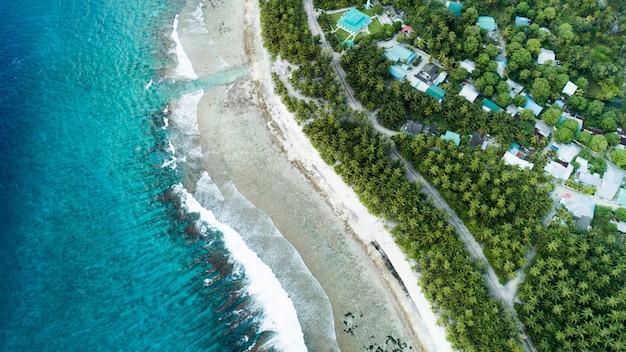 Воздушная съемка пляжа с волнами от моря и джунглей мальдивских островов