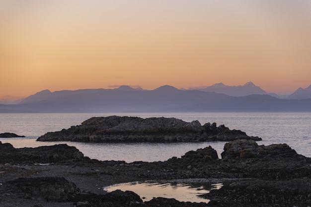 Красивый выстрел из скалистых утесов возле моря под розовым небом