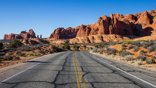 Красивая съемка пустой дороги посреди пустыни с кустами и скалами на расстоянии